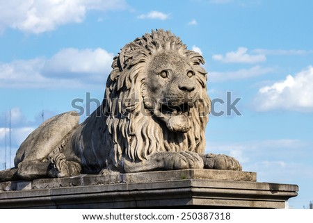Decorative stone lion on one of the pillars of the bridge in Budapest, Hungary. Bright sunny day and blue sky - stock photo