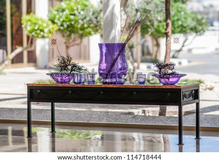 decorative table with purple vases against the window - stock photo