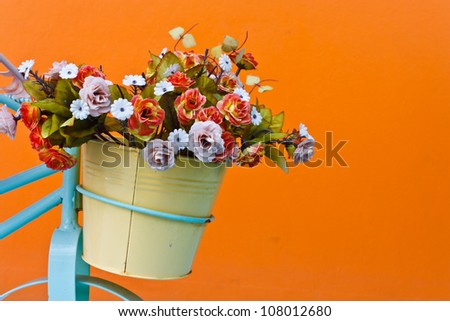 decorative the bicycle with artificial flowers on color wall background - stock photo