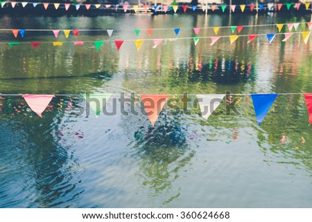 Decorative triangular flags on river at Thailand - Vintage effect style pictures - stock photo