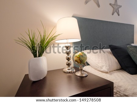 Decorative vase, night lamp and globe on the night stand table in bedroom.  Interior design.