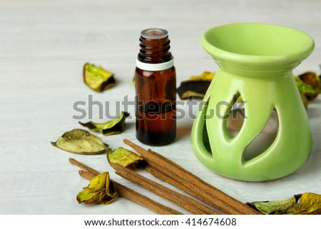 decorative vase with a candle and a jar with essential oils with the incense on white wooden background - stock photo