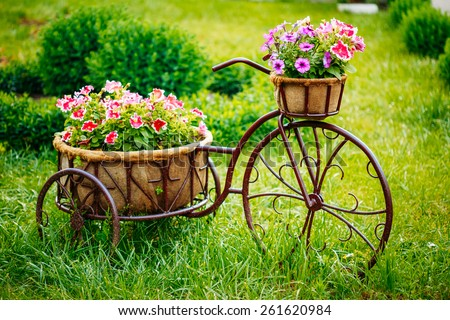 Decorative Vintage Model Old Bicycle Equipped Basket Flowers Garden. Toned Photo. - stock photo