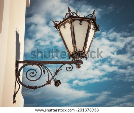 decorative  wall street lamp on blue sky background - stock photo