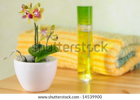 Decorative wellness set with orchid in focus, perfume and towel in the background - stock photo