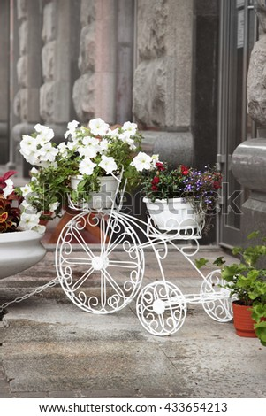 Decorative white bicycle with flowers standing on the street of the town.