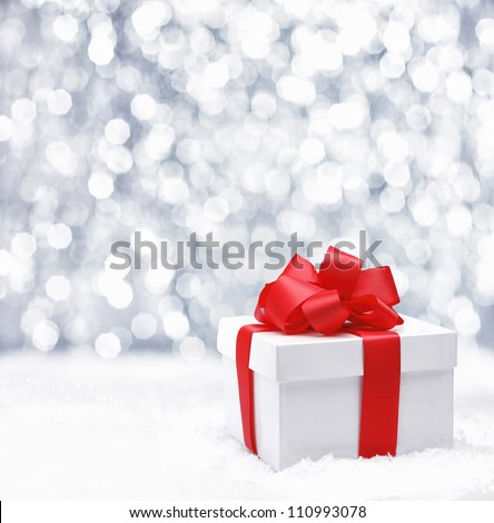 Decorative white gift box with a large red bow standing in fresh snow against a background bokeh of twinkling party lights - stock photo