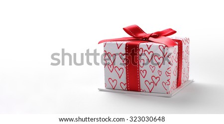 Decorative white gift box with red ribbon and painted hearts. Front view. White isolated background