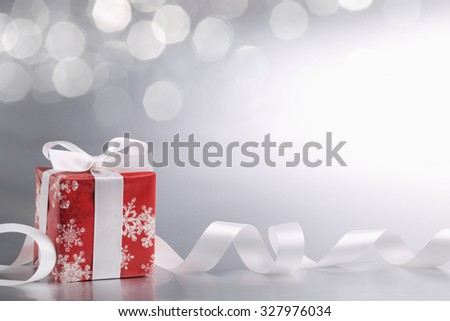 Decorative white gift box with ribbon against abstract background.