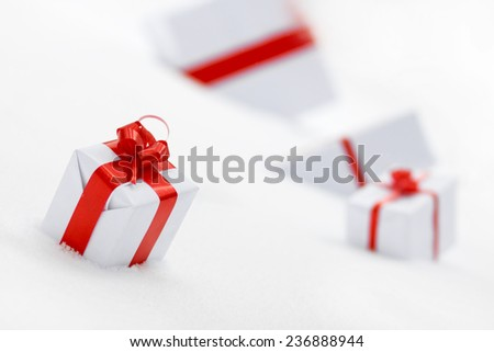 Decorative white gift boxes with a red bow standing in fresh snowDecorative white gift boxes with a red bow standing in fresh snow - stock photo