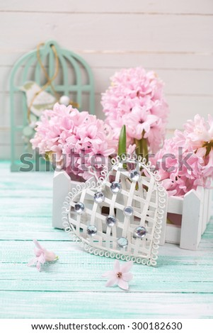 Decorative white heart and pink hyacinths  in box on  turquoise wooden background. Selective focus is on heart.