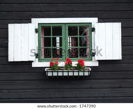 Decorative window of wooden cabin. Old wooden house in Norway. Decorative window with flowers. - stock photo