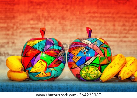 decorative wooden apples and bananas on bright abstract background. Apples are made and painted by hand