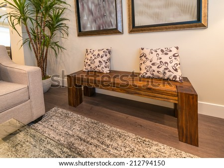 Decorative wooden bench with some pillows on it as an element of the interior design. - stock photo