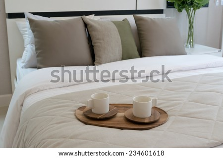 Decorative wooden tray with tea set on bed - stock photo