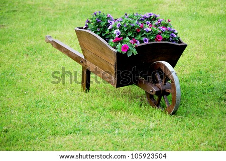 decorative wooden wheelbarrow with flowers in green grass - stock photo