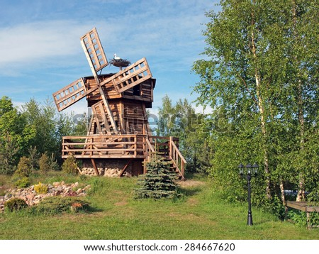 Decorative wooden windmill in park and stork in the nest, horizontal  - stock photo