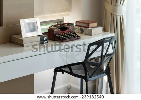 decorative working table with typewriter and books - stock photo