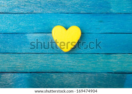 Decorative yellow heart on blue wooden background - stock photo
