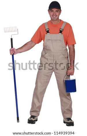 Decorator holding a paint roller with long extension - stock photo