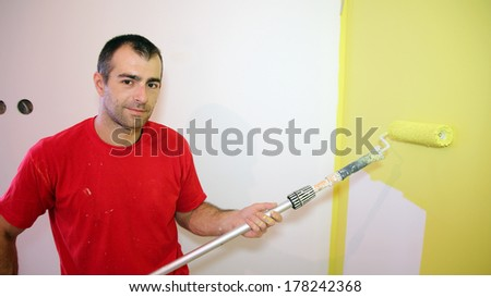 Decorator Holding Paint Roller. House Painter. Man using a long roller to paint a wall in yellow. - stock photo