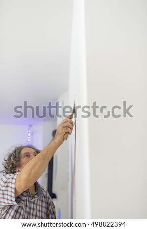 Decorator retouching imperfections in a newly painted clean white wall with a small spatula in a DIY or renovations concept.