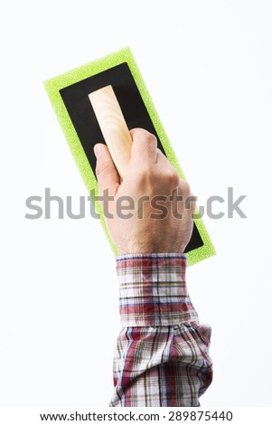 Decorator's male hand holding a painting pad, diy and home renovation concept - stock photo