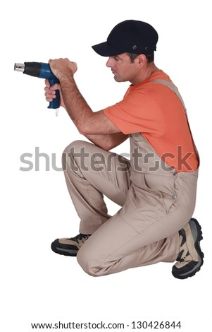 Decorator with a heat gun - stock photo