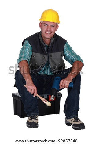 Decorator with a paint brush and blowtorch - stock photo