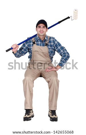 Decorator with a paint roller - stock photo