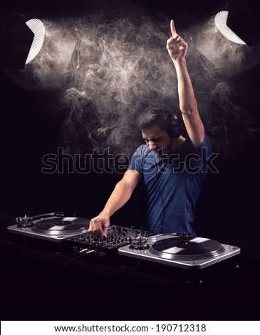 Deejay being excited while playing music from vinyl with one raised hand. He is illuminated by two vintage spot light reflectors. - stock photo