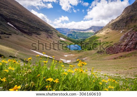Deep blue alpine lake in a mountain valley framed by yellow wildflowers in Glacier National Park, Montana - stock photo