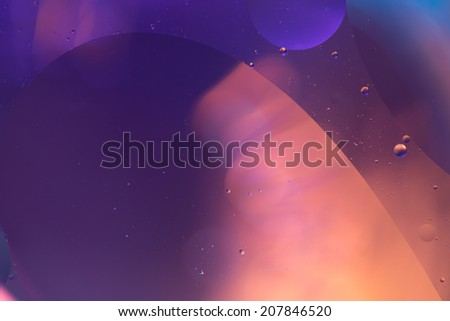Deep Blue and golden water mix with a wave-like shape in front of a blurred background. - stock photo