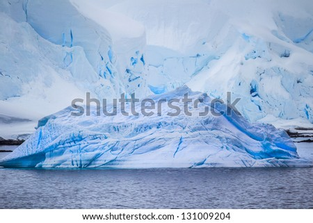 Deep blue iceberg in the foreground - stock photo