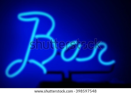 Deep blue neon light bar sign, with a soft focus applied to it. - stock photo