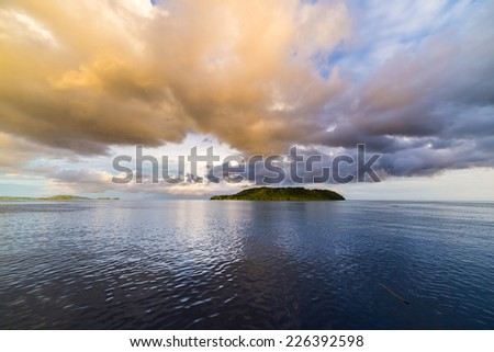 Deep blue sea and dramatic sky with colorful clouds at dusk in the remote Togean Islands, Central Sulawesi, Indonesia. Wide angle view from offshore. - stock photo
