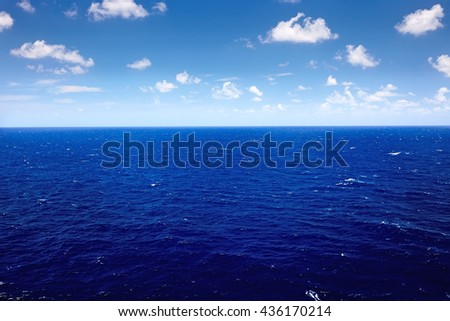 deep blue sea with blue sky and cloud - stock photo
