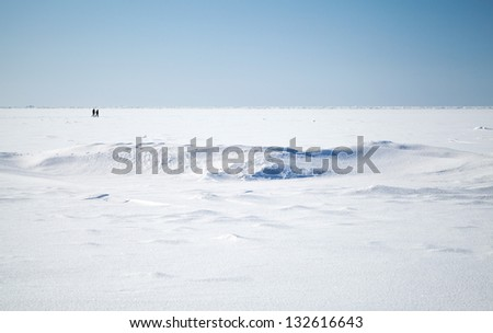 Deep blue sky and snow on frozen Baltic Sea with people walking on ice