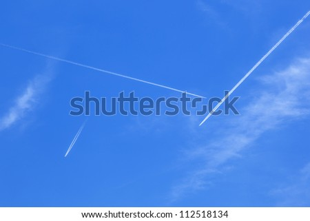 Deep blue sky with many  contrails - stock photo
