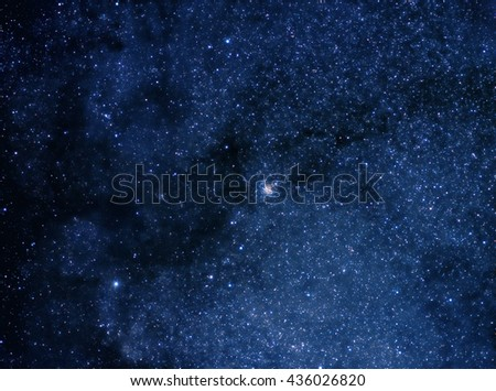 Deep blue space background filled with nebulae and myriads of stars - stock photo