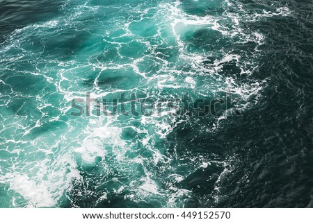 Deep blue stormy sea water surface with foam and waves pattern, background photo texture