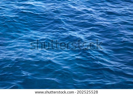 Deep blue water background in blue - empty and nobody - just waves. - stock photo
