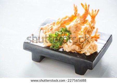 deep fried almond shrimp tempura on black plate - stock photo