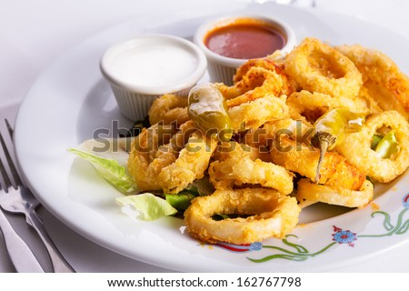 Deep fried breaded calamaris served with white and red sauce and topped with hot pepper pickles - stock photo