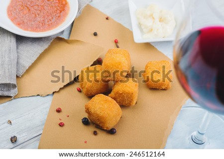Deep fried cheese balls on a wooden table with souce and glass of red wine - stock photo