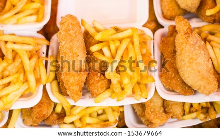 Deep fried chicken and chips in foam box - stock photo