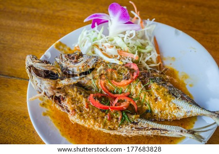 Deep fried fish with curry sauce on white plate