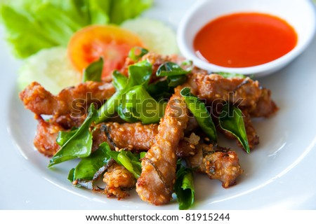 Deep fried pork with leech lime leaf and chili sauce - stock photo