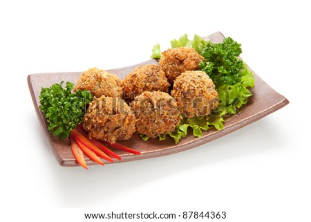 Deep Fried Salmon Croquette. Garnished on Salad Leaf with Bell Pepper and Parsley - stock photo