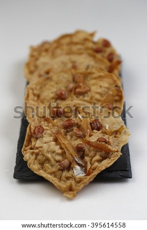deep-fried savoury Javanese Rempeyek peyek cracker made from crispy rice flour batter includes peanut and bilis anchovies and udang ebi shrimps served as tea or during festivities
